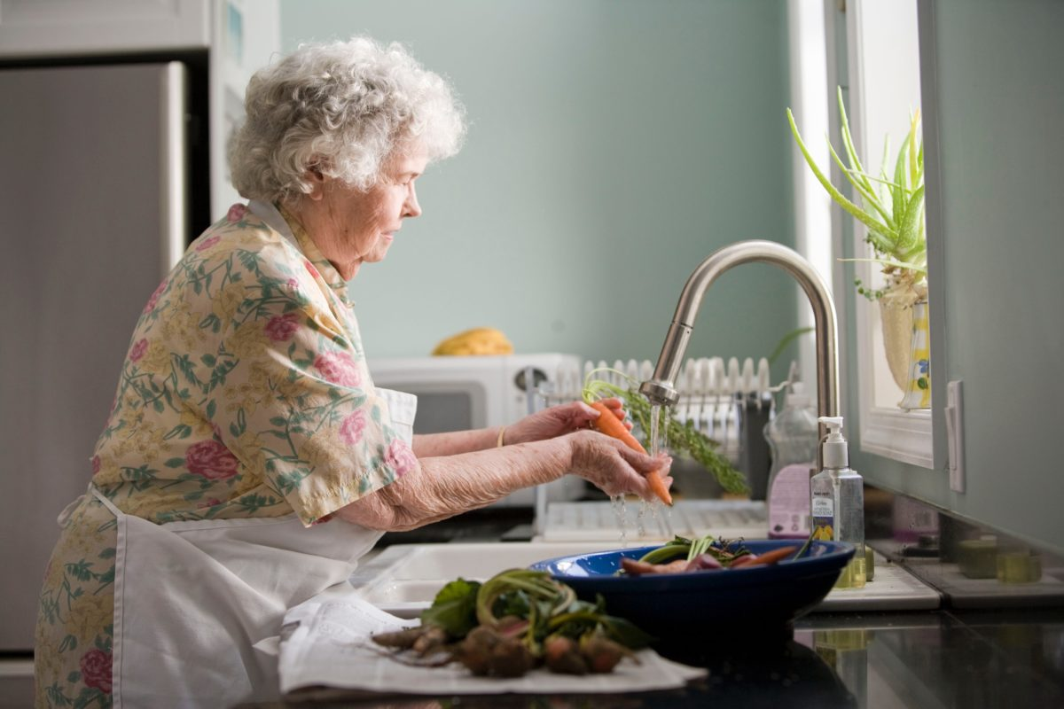 senior woman at kitchen sink